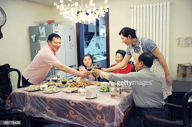 This picture taken on May 12 2013 shows Chi Shubo drinking a toast with relatives at his home in Beijing With two cars foreign holidays and a cook...