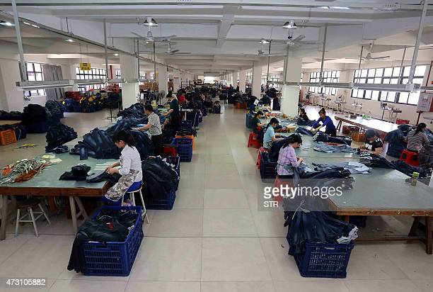 This picture taken on May 12 2015 shows Chinese workers making jeans at a clothing factory in Shishi east China's Fujian province Retail sales growth...