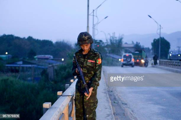 This picture taken on May 12 2018 shows an armylinked militiaman securing a bridge in Muse China on May 13 condemned fighting on its border between...