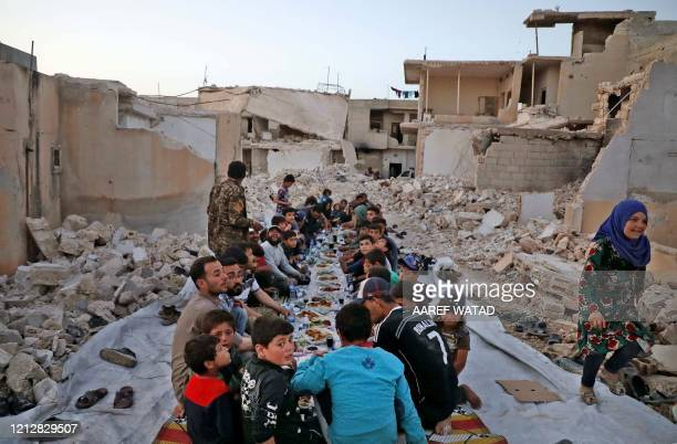 This picture taken on May 12, 2020 in the village of Kafr Nuran in the western countryside of Syria's northern Aleppo province shows men and children...