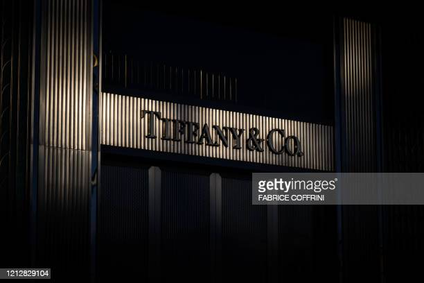 This picture taken on May 12 in Geneva shows the sunset reflecting on a sign of a closed store of US luxury jewelry retailer Tiffany & Co. After...