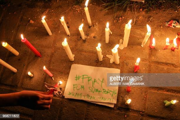 This picture taken on May 13 2018 shows a candlelight vigil in the city of Medan on Indonesia's Sumatra island to support the victims and their...