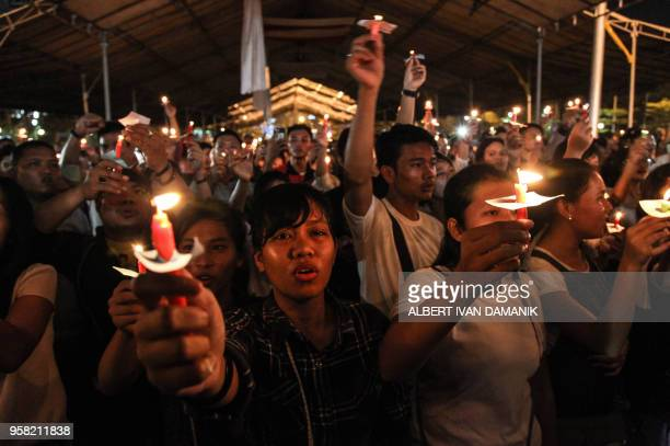 TOPSHOT This picture taken on May 13 2018 shows a candlelight vigil in the city of Medan on Indonesia's Sumatra island to support the victims and...