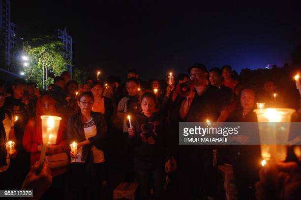 This picture taken on May 13 2018 shows a candlelight vigil in the city of Bandung West Java to support the victims and their relatives after a...