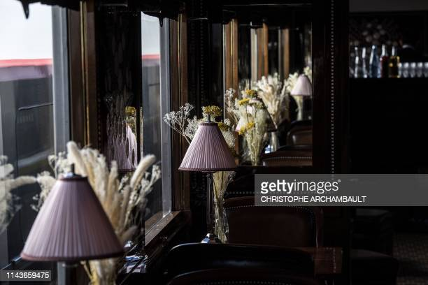 This picture taken on May 13, 2019 shows table lamps and flowers adorning the dining car of a restored carriage of an Orient Express train displayed...