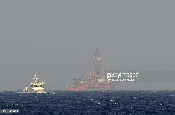 This picture taken on May 14 2014 from a Vietnamese coast guard ship shows a Chinese coast guard vessel sailing near China's oil drilling rig in...
