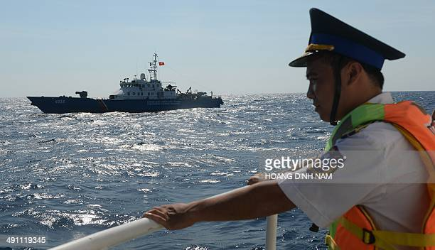 This picture taken on May 14 2014 shows a Vietnamese coast guard officer looking towards a Vietnamese Coast Guard ship sailing near the area of...
