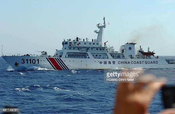 This picture taken on May 14 2014 shows a Vietnamese coast guard officer taking pictures of a Chinese coast guard vessel near China's oil drilling...