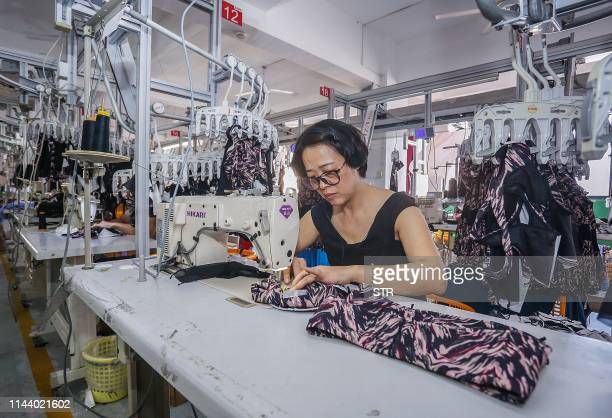 This picture taken on May 14 2019 shows a worker making clothes for export at a factory in Quanzhou in China's eastern Fujian province / China OUT