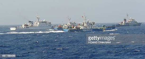 This picture taken on May 15 2014 shows a Chinese coast guard ship being blocked by three Vietnamese coast guard vessels near China's oil drilling...