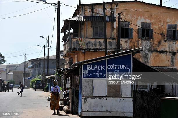 This picture taken on May 17 2012 shows a young boy playing with a ball and a woman standing in a street in GrandBassam a historical town 40 km east...