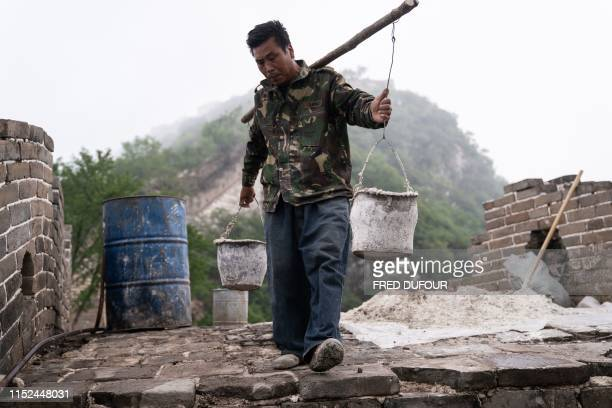TOPSHOT This picture taken on May 17 2019 shows a worker carrying buckets at a restored part of the Great Wall in Xiangshuihu in Huairou District on...