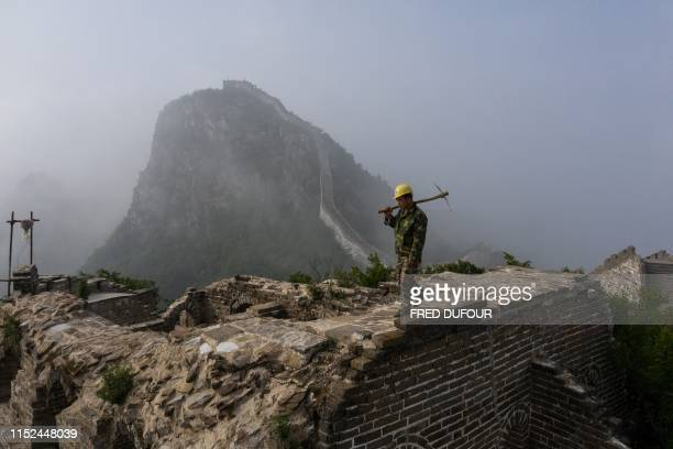 TOPSHOT This picture taken on May 17 2019 shows a worker inspecting at a restored part of the Great Wall in Xiangshuihu in Huairou District on the...