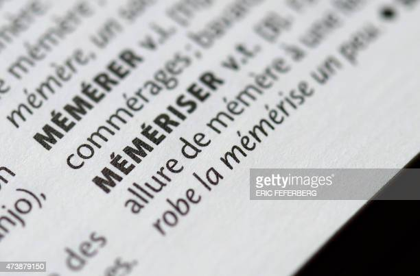 This picture taken on May 18 2015 shows the latest edition of the French dictionary 'Le Petit Larousse' dictionary held open at the page to display...