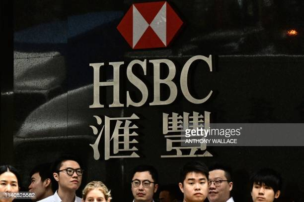 This picture taken on May 2, 2019 shows pedestrians waiting to cross a road as they stand under HSBC signage outside one of the bank's branches in...
