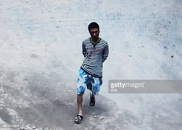 This picture taken on May 20 2014 from a security video shows the 35yearold suspect a man surnamed Chen making his way into the school before going...