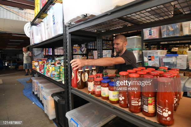 This picture taken on May 20, 2020 shows volunteer Mathew Hatcher arranging food items on shelves at his warehouse in Batemans Bay, on the south...