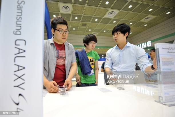 This picture taken on May 21, 2013 shwos visitors looking at Samsung Electronics smartphone Galaxy S4 during an IT show in Seoul. South Korea's...