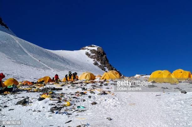 This picture taken on May 21, 2018 shows discarded climbing equipment and rubbish scattered around Camp 4 of Mount Everest. - Decades of commercial...