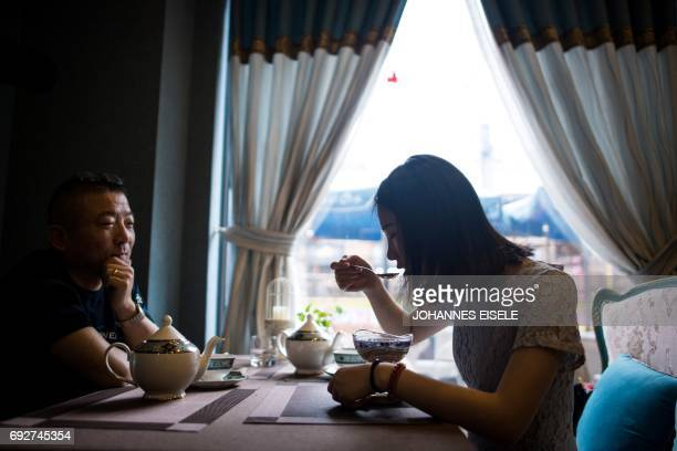 This picture taken on May 23 2017 shows a woman eating a birds nest dessert in the NestCha restaurant in Shanghai The cries of amorous swiftlets echo...