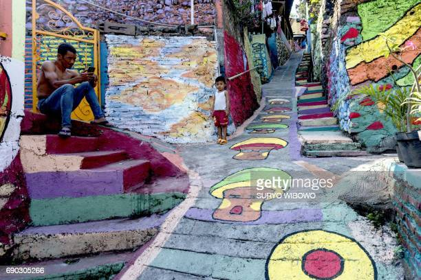 This picture taken on May 23 2017 shows villagers relax along a path at an Indonesian hamlet dubbed 'the rainbow village' in Semarang central Java...