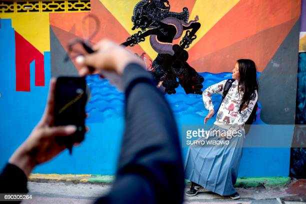 This picture taken on May 23 2017 shows visitors posing for photos along a path at an Indonesian hamlet dubbed 'the rainbow village' in Semarang...