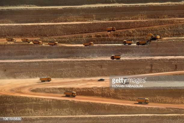 TOPSHOT This picture taken on May 23 2018 shows trucks transporting soil in an openpit coal mining site at Islamkot in the desert in the Tharparkar...