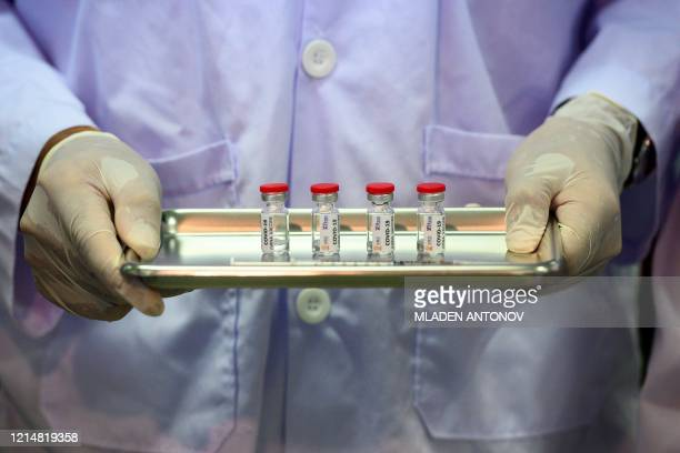 This picture taken on May 23, 2020 shows a laboratory technician holding a tray with doses of a COVID-19 novel coronavirus vaccine candidate ready...