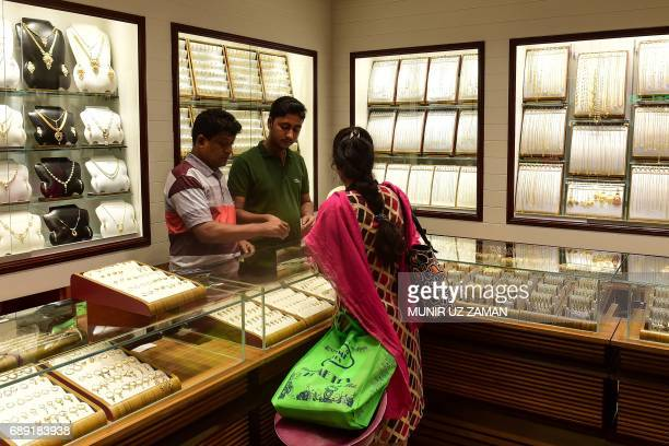 This picture taken on May 24 2017 shows a shopper browsing in a gold jewelry shop in Dhaka Gold smuggling in Bangladesh is at a record high officials...