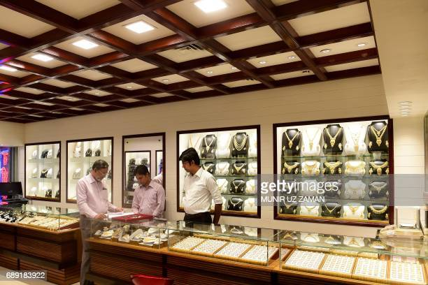 This picture taken on May 24 2017 shows salesmen waiting for customers at a gold jewelry shop in Dhaka on May 24 2017 Gold smuggling in Bangladesh is...