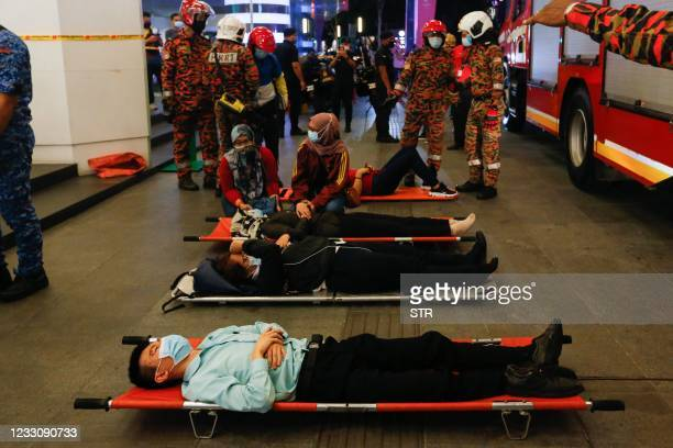 This picture taken on May 24, 2021 shows injured passengers lying on stretchers outside KLCC station after an accident involving two Light Rail...