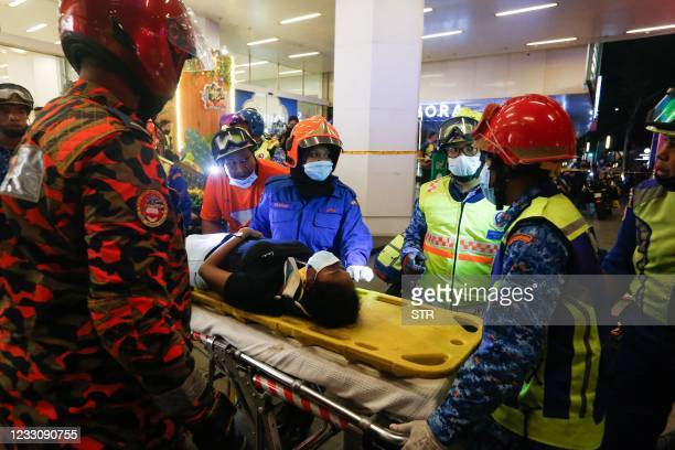 This picture taken on May 24, 2021 shows rescue personnel tending to an injured passenger ooutside KLCC station after an accident involving two Light...