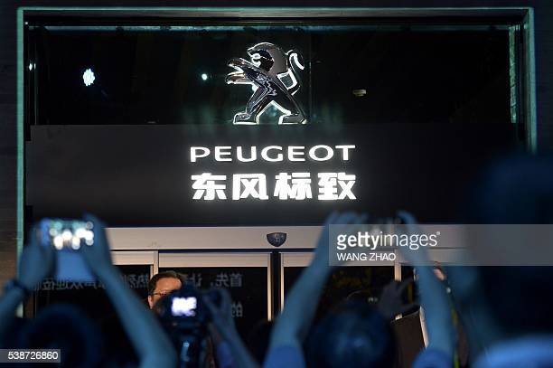 This picture taken on May 25 2016 shows visitors taking pictures at the entrance of a Peugeot showroom during its opening ceremony in Beijing The...