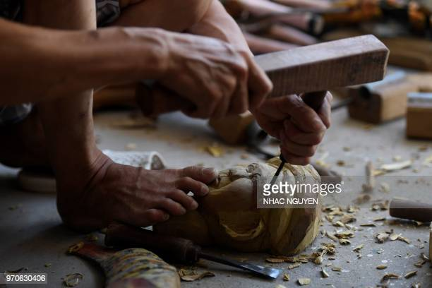 This picture taken on May 25 2018 shows a Vietnamese craftsman carving a wood to make a water puppet at a workshop in Thai Binh province Vietnam is...