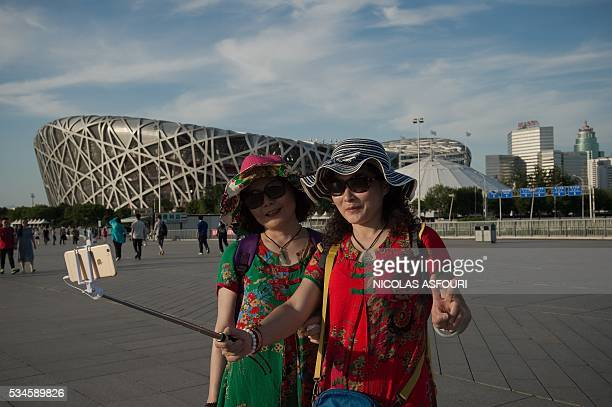 This picture taken on May 26 2016 shows two Chinese women taking a selfie with a smartphone outside the National Olympic Stadium known as the Bird's...