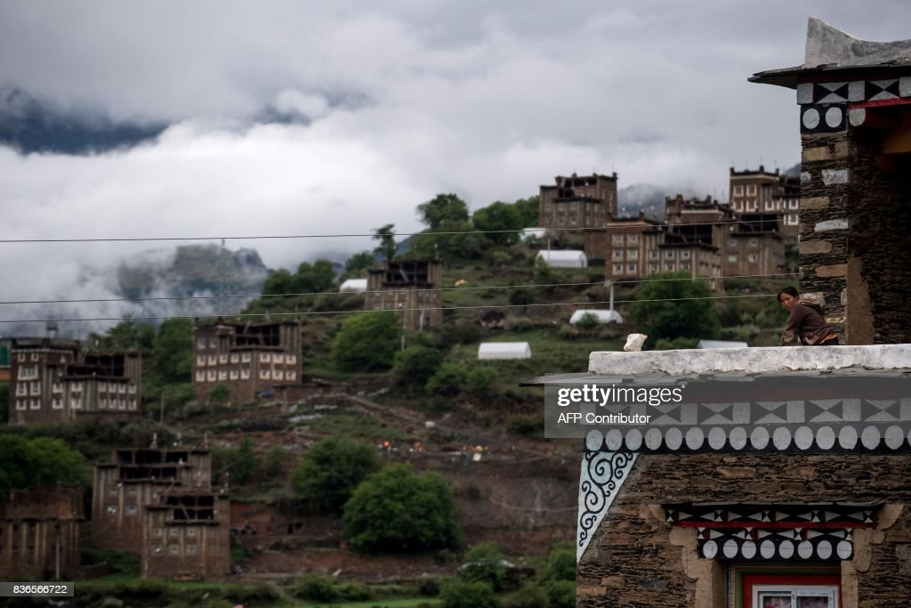 This picture taken on May 28, 2017 shows a daughter of 60-year-old matriarch Dolma Lhamo standing in the balcony of a house in Zhaba in the valley of the Yalong River in Daofu County of the Garze Tibetan Autonomous Prefecture. The small matrilineal Zhaba ethnic group of Sichuan province eschew monogamous relationships for traditional 'walking marriages' -- so-called since men typically walk to their rendezvous before slipping through their lover's window. But the arrival of the internet, smartphones, livestreaming and popular Korean TV shows, along with improved transportation and education opportunities beyond the valley, have exposed the isolated Zhaba to other lifestyles. / AFP PHOTO / Johannes EISELE / TO