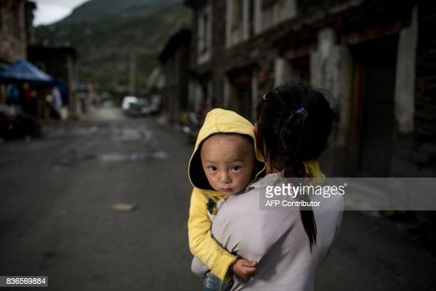 This picture taken on May 28 2017 shows a girl carrying a boy in Zhaba in the valley of the Yalong River in Daofu County of the Garze Tibetan...