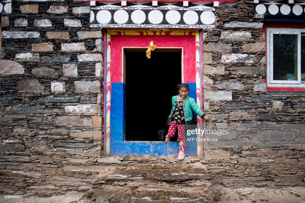 This picture taken on May 28, 2017 shows a girl coming out of a building in Zhaba in the valley of the Yalong River in Daofu County of the Garze Tibetan Autonomous Prefecture. The small matrilineal Zhaba ethnic group of Sichuan province eschew monogamous relationships for traditional 'walking marriages' -- so-called since men typically walk to their rendezvous before slipping through their lover's window. But the arrival of the internet, smartphones, livestreaming and popular Korean TV shows, along with improved transportation and education opportunities beyond the valley, have exposed the isolated Zhaba to other lifestyles. / AFP PHOTO / Johannes EISELE / TO