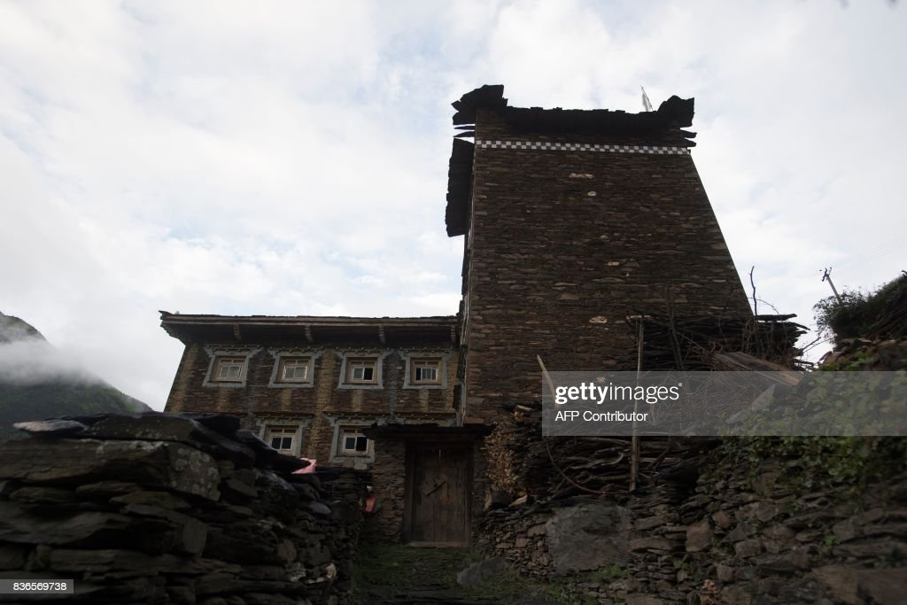 This picture taken on May 28, 2017 shows a house in Zhaba in the valley of the Yalong River in Daofu County of the Garze Tibetan Autonomous Prefecture. The small matrilineal Zhaba ethnic group of Sichuan province eschew monogamous relationships for traditional 'walking marriages' -- so-called since men typically walk to their rendezvous before slipping through their lover's window. But the arrival of the internet, smartphones, livestreaming and popular Korean TV shows, along with improved transportation and education opportunities beyond the valley, have exposed the isolated Zhaba to other lifestyles. / AFP PHOTO / Johannes EISELE / TO