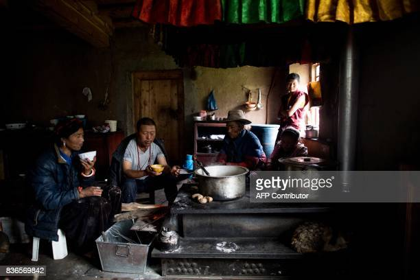 This picture taken on May 28 2017 shows a woman and her family having a breakfast consisting of yak butter tea and tsampa in their kitchen in Zhaba...
