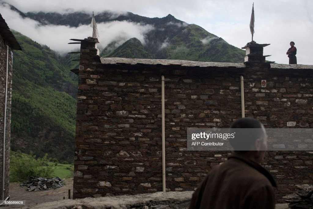 This picture taken on May 28, 2017 shows a woman standing on top of a house in Zhaba in the valley of the Yalong River in Daofu County of the Garze Tibetan Autonomous Prefecture. The small matrilineal Zhaba ethnic group of Sichuan province eschew monogamous relationships for traditional 'walking marriages' -- so-called since men typically walk to their rendezvous before slipping through their lover's window. But the arrival of the internet, smartphones, livestreaming and popular Korean TV shows, along with improved transportation and education opportunities beyond the valley, have exposed the isolated Zhaba to other lifestyles. / AFP PHOTO / Johannes EISELE / TO