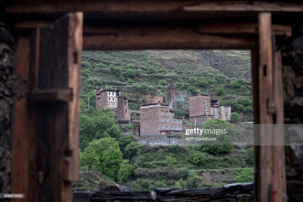This picture taken on May 28, 2017 shows houses in Zhaba in the valley of the Yalong River in Daofu County of the Garze Tibetan Autonomous Prefecture. The small matrilineal Zhaba ethnic group of Sichuan province eschew monogamous relationships for traditional 'walking marriages' -- so-called since men typically walk to their rendezvous before slipping through their lover's window. But the arrival of the internet, smartphones, livestreaming and popular Korean TV shows, along with improved transportation and education opportunities beyond the valley, have exposed the isolated Zhaba to other lifestyles. / AFP PHOTO / Johannes EISELE / TO