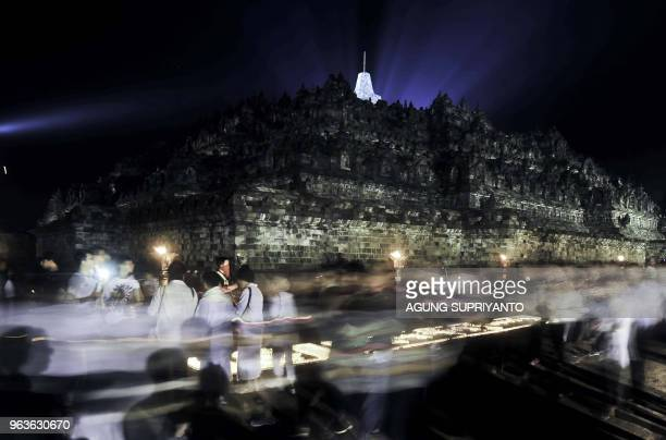 This picture taken on May 29 2018 shows Buddhist monks and devotees conducting prayers at the Borobudur temple in Magelang Central Java on Vesak Day...