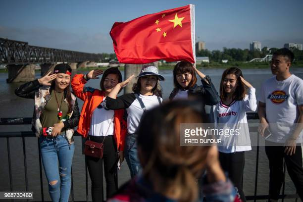 This picture taken on May 29 2018 shows Chinese tourists taking pictures on the Broken Bridge in the border city of Dandong in China's northeast...