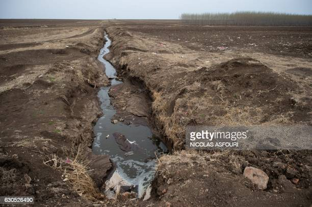 This picture taken on May 3 2016 shows a pipe releasing waste water into fields surrounding a dairy farm in Gannan county Heilongjiang province Giant...