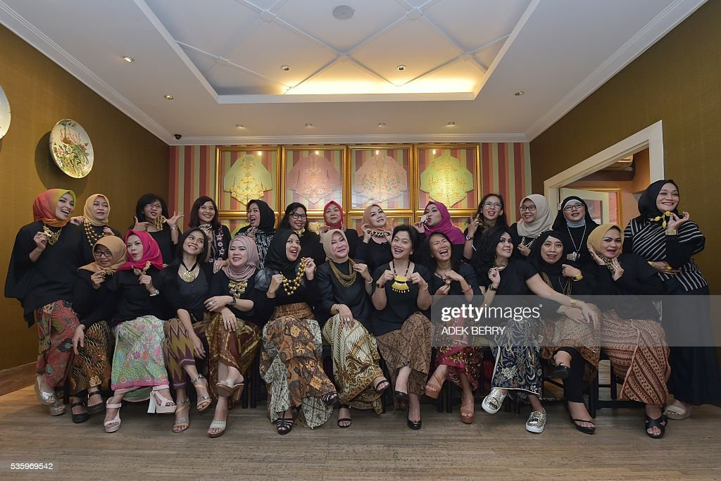 This picture taken on May 30, 2016 shows Indonesian women, clad in traditional batik attire, posing in a gruop photo following a lottery during their 'arisan' in Jakarta. Arisan is a social gathering of people with an agreement to regularly pay a fixed amount of money, with individuals taking turns in receiving funds by lot for each members. The tradition serves as a form of microfinance among some unbanked Indonesians and strengthens relationships within their social group. / AFP / ADEK
