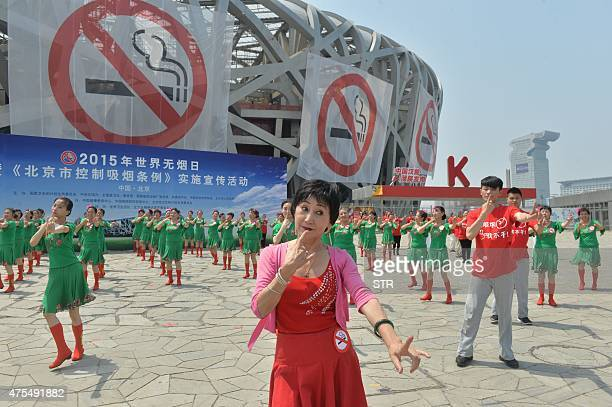 This picture taken on May 31 2015 shows a group of people dancing to popularise antismoking measures before giant 'no smoking' banners at the...