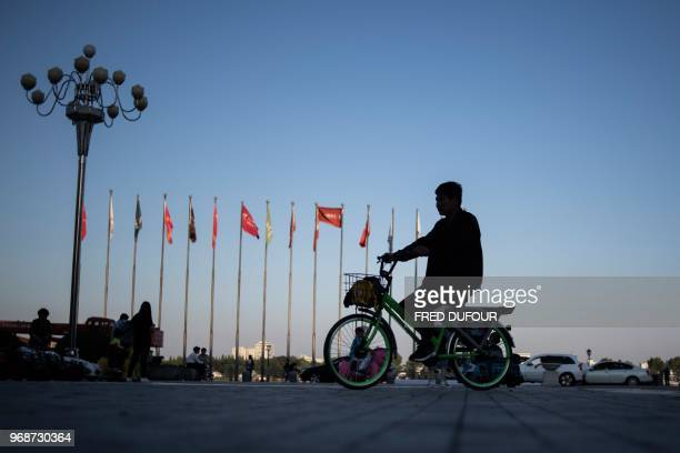 TOPSHOT This picture taken on May 31 2018 shows a man riding his bike in the border city of Dandong in China's northeast Liaoning province Beijing an...