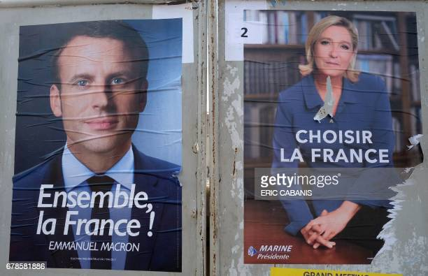 This picture taken on May 4 2017 in VillefranchedeLauragais near Toulouse shows election campaign posters of French presidential candidates Emmanuel...