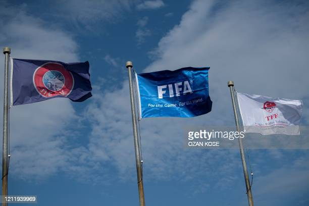 This picture taken on May 6 2020 in Istanbul shows flags of of Turkish Football Federation FIFA and UEFA at the entrance of the organization's...